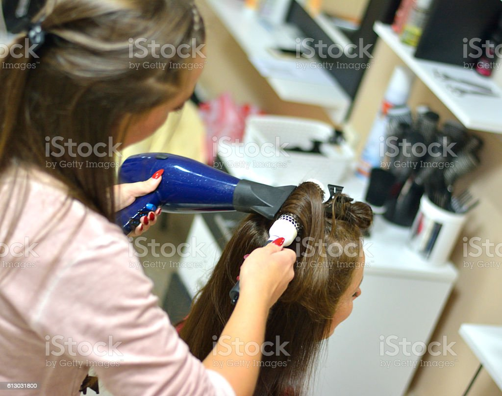 Female Hairdresser Using Hairbrush and Hair Dryer in Hair Salon stock photo