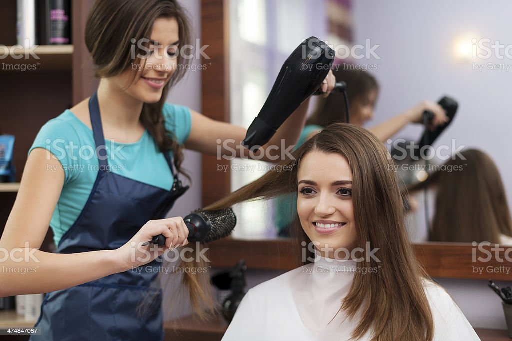 Female hairdresser using hairbrush and hair dryer stock photo