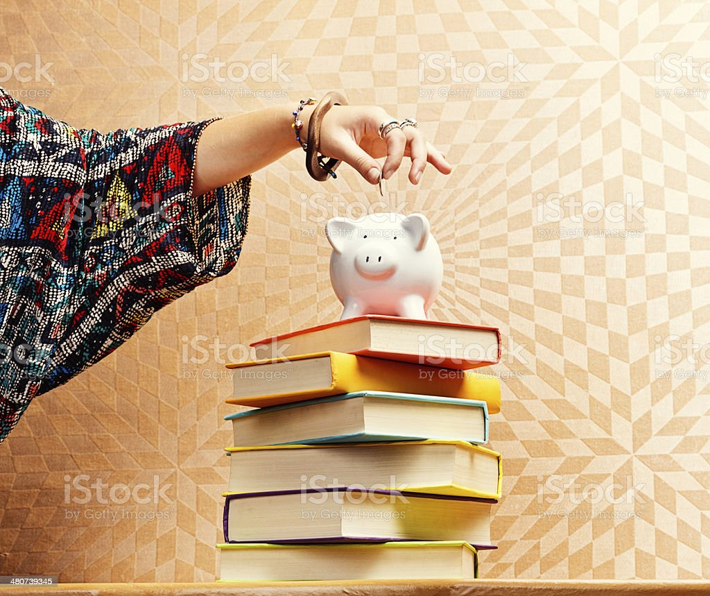 Female hand adds coin to piggybank on book stack stock photo