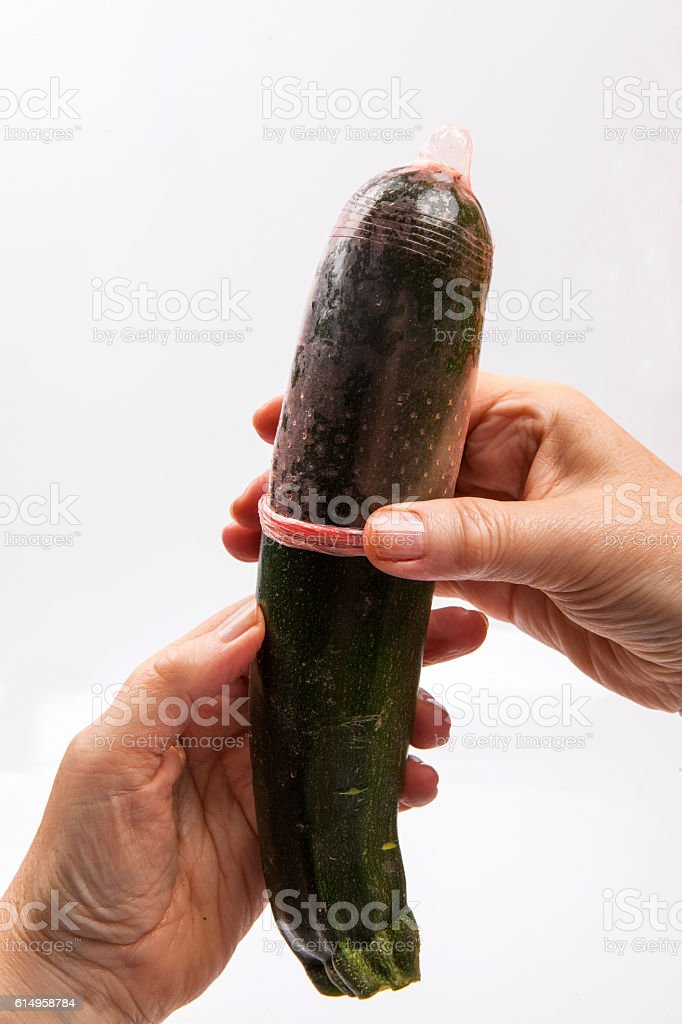 Female hand adjusting a condom on a cucumber stock photo