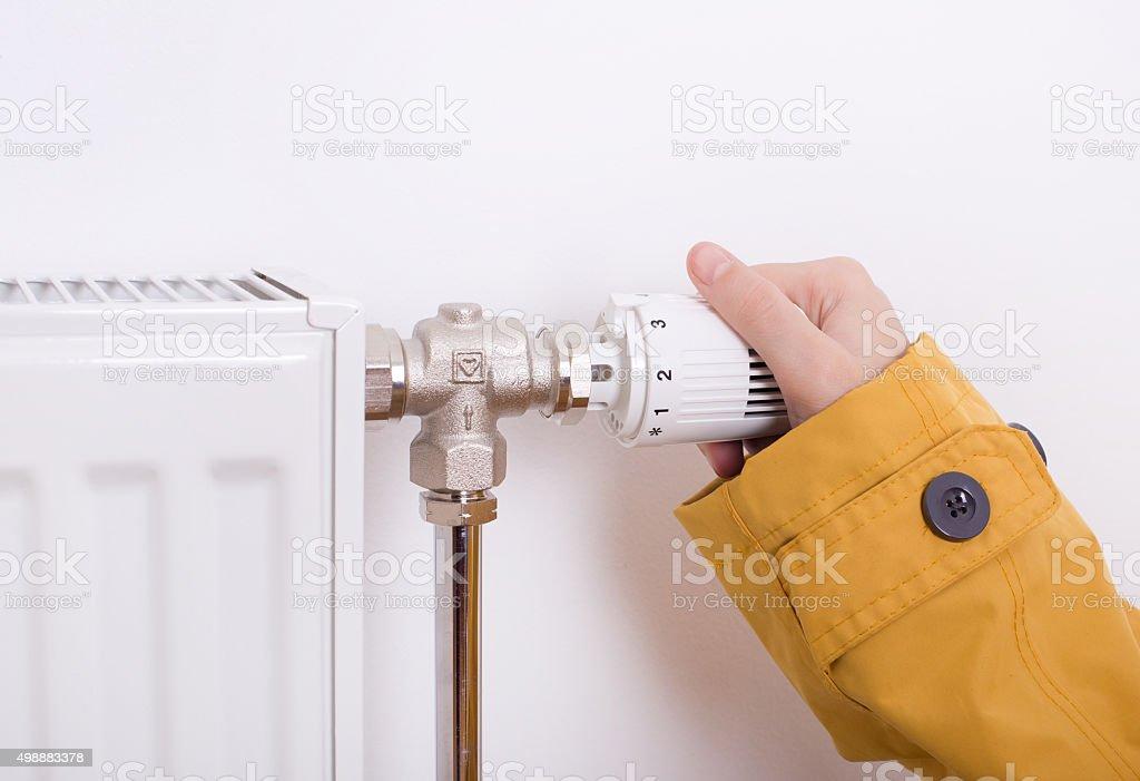 Female hand adjusting heater stock photo