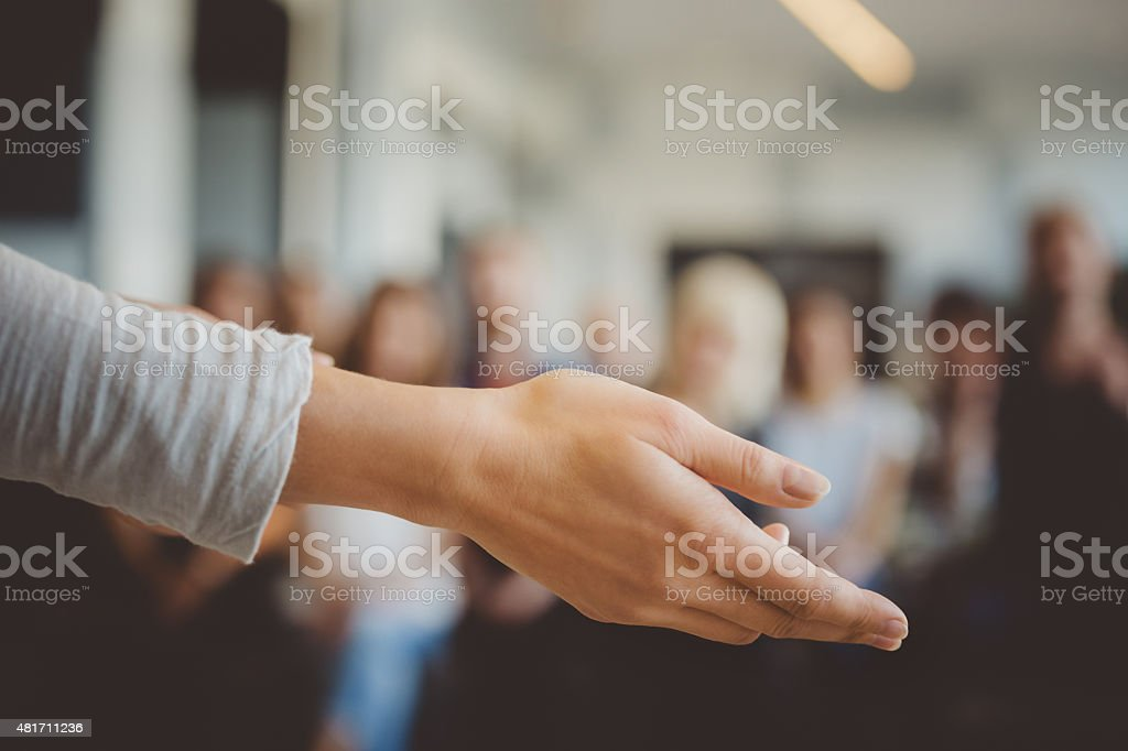 Female hand against defocused group of students stock photo
