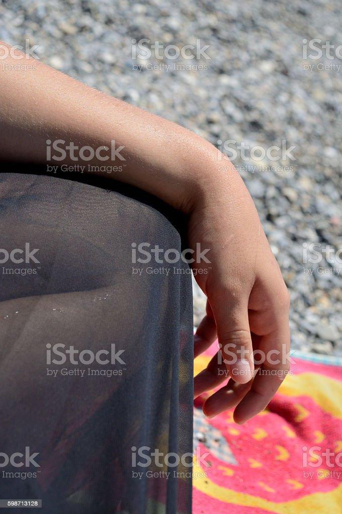 Female hand and leg on the beach stock photo