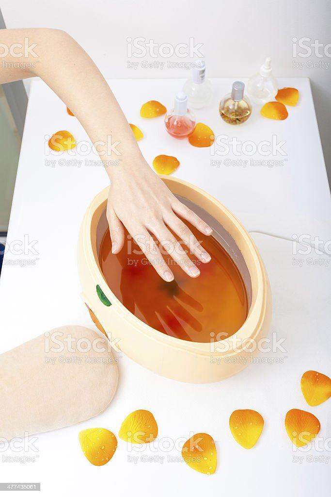 Female hand and paraffin wax bowl. Woman in beauty salon stock photo