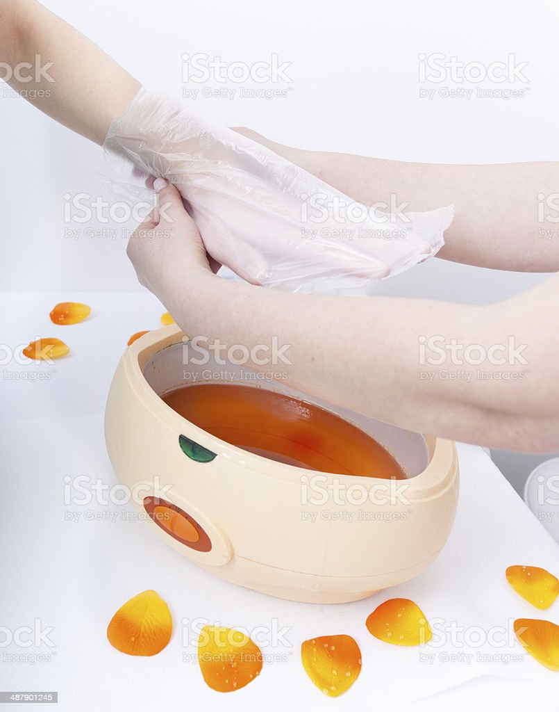 Female hand and paraffin wax bowl. Woman in beauty salon royalty-free stock photo