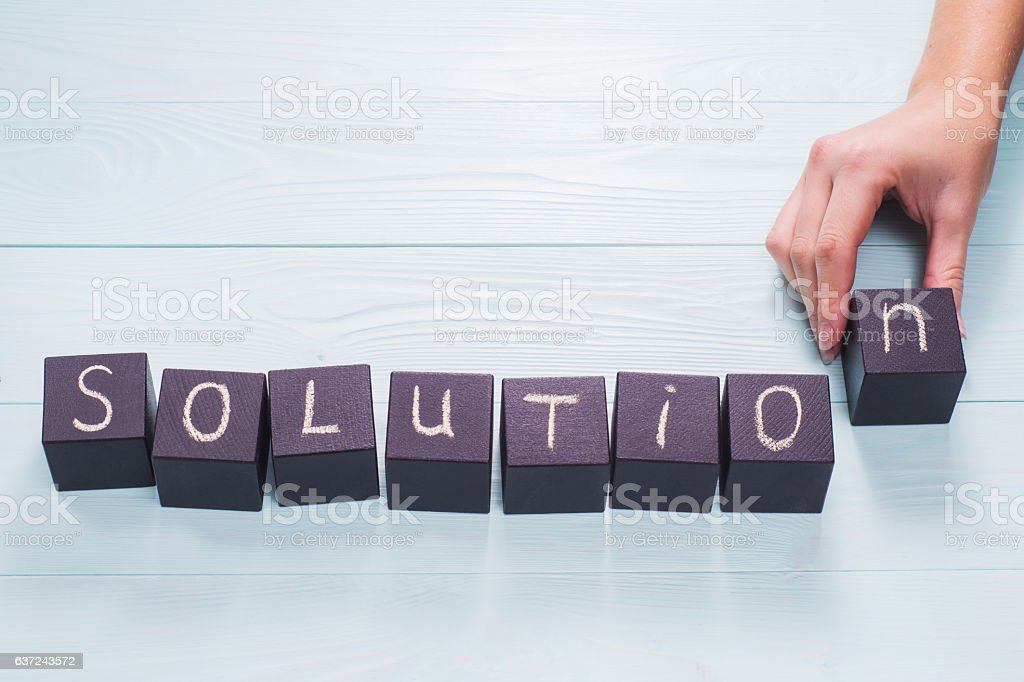 Female hand arrange wood letters as Solution word stock photo