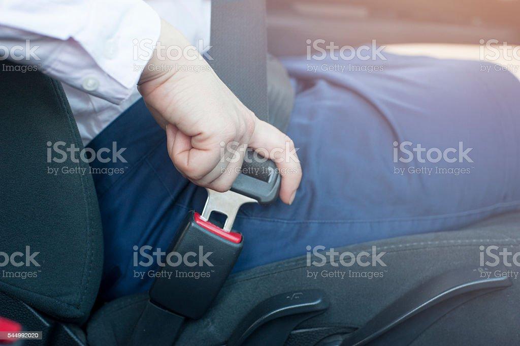 Female hand buckling up her seat belt stock photo