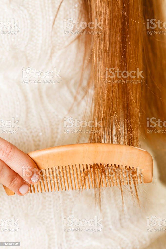 Female hand combing long hair. stock photo