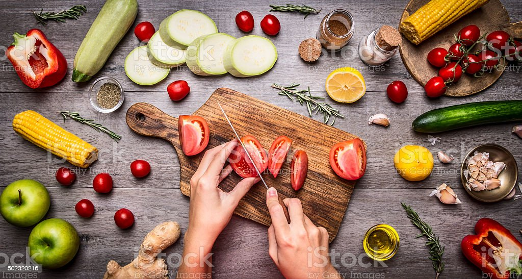 Female hand cut tomatoes on vegetarian food concept. stock photo