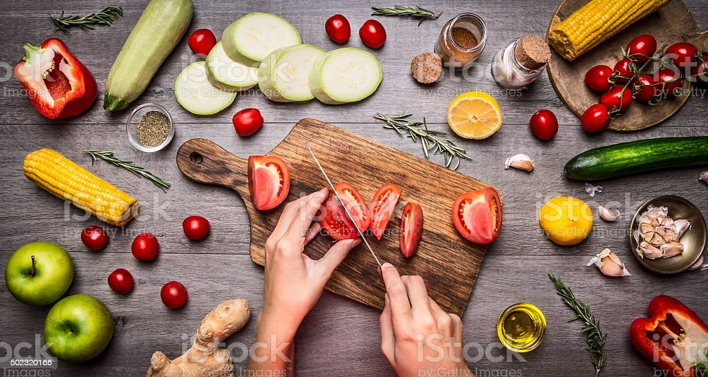 Female hand cut tomatoes rustic kitchen table,vegetarian concept. stock photo