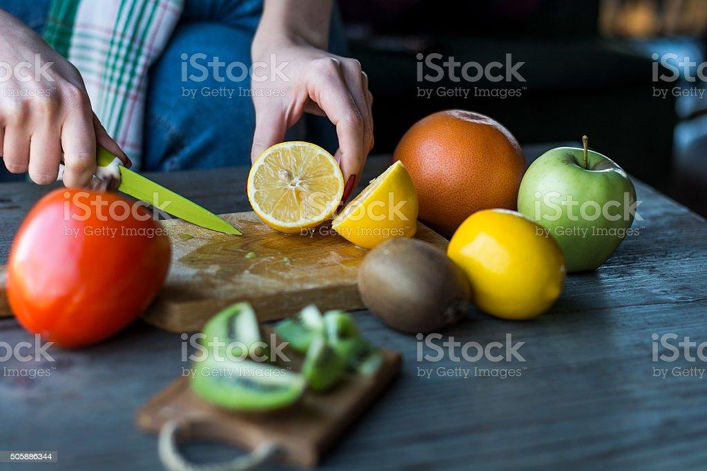 Female hand cuts fresh lemon stock photo