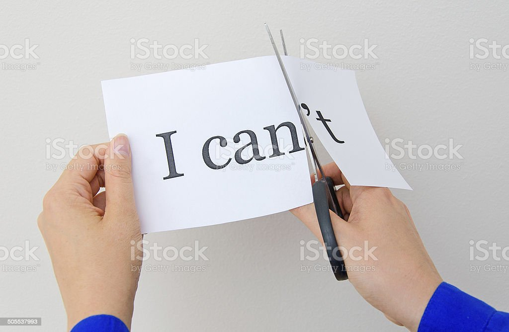 Female hand cutting paper with words. Concept. stock photo