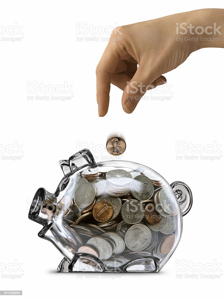 Female Hand Dropping Coin Into Full Clear Piggy Bank Isolated royalty-free stock photo