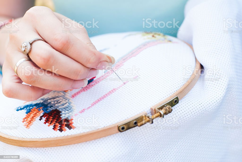 Female hand embroiders angels in the hoop. stock photo