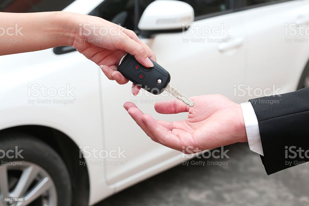 Female hand giving a key for buyer or rental car. stock photo