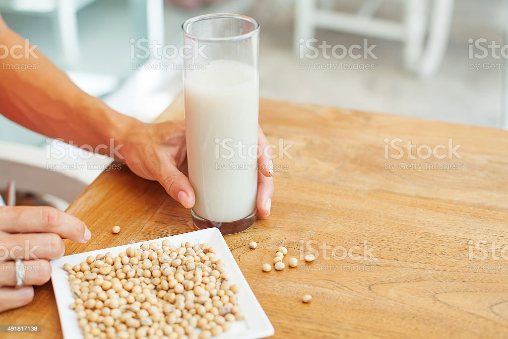 female hand holding a glass of soya milk stock photo