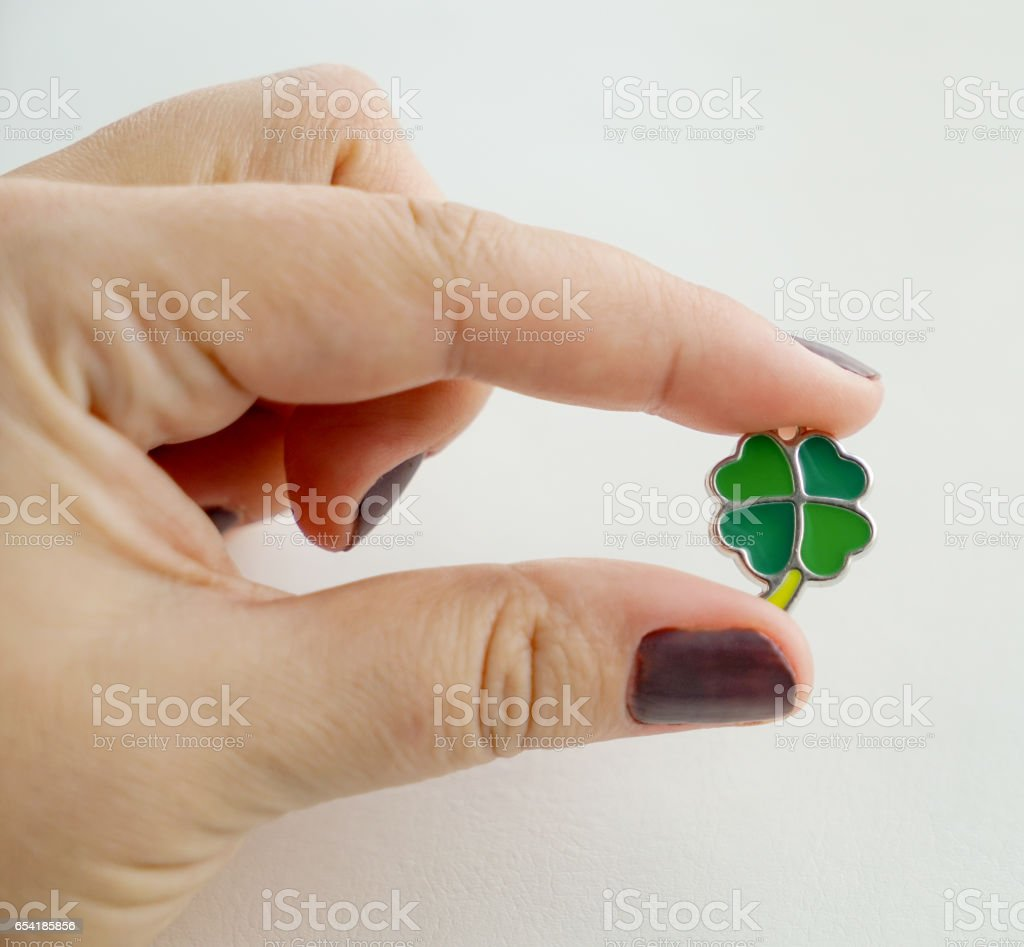 Female hand holding a leaf clover charm stock photo