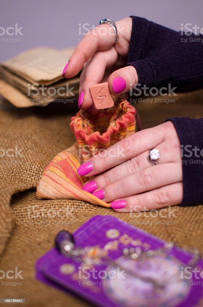 female hand holding a magic rune plate stock photo