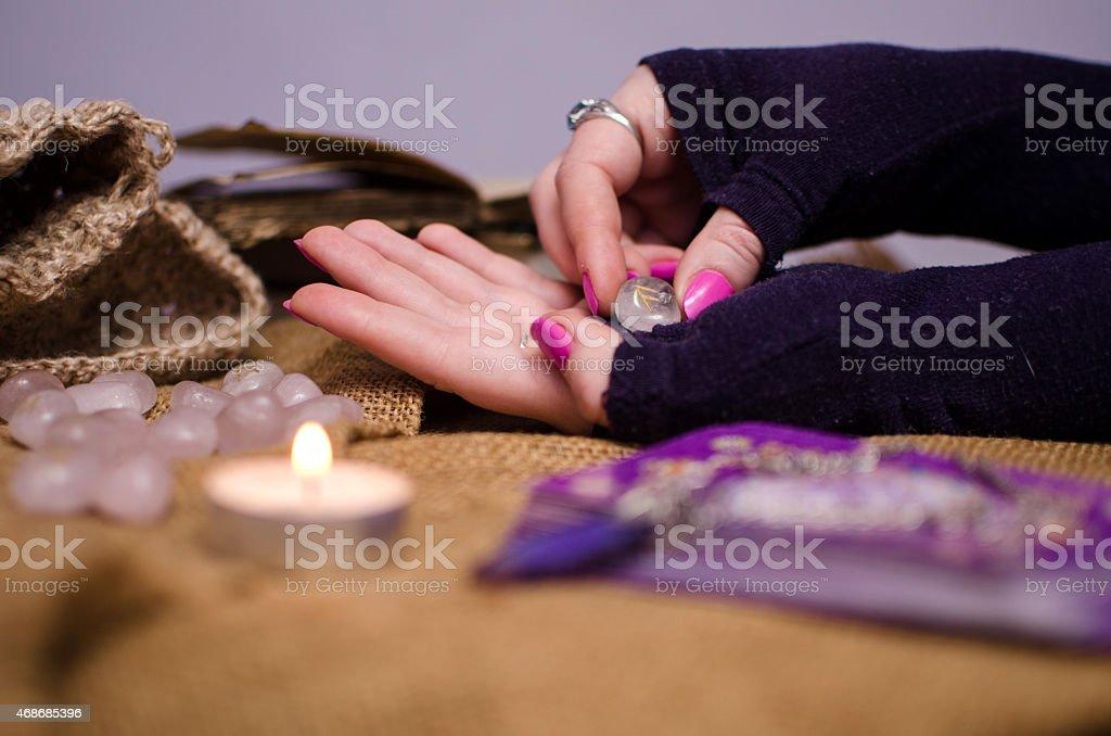 female hand holding a magic rune stone stock photo