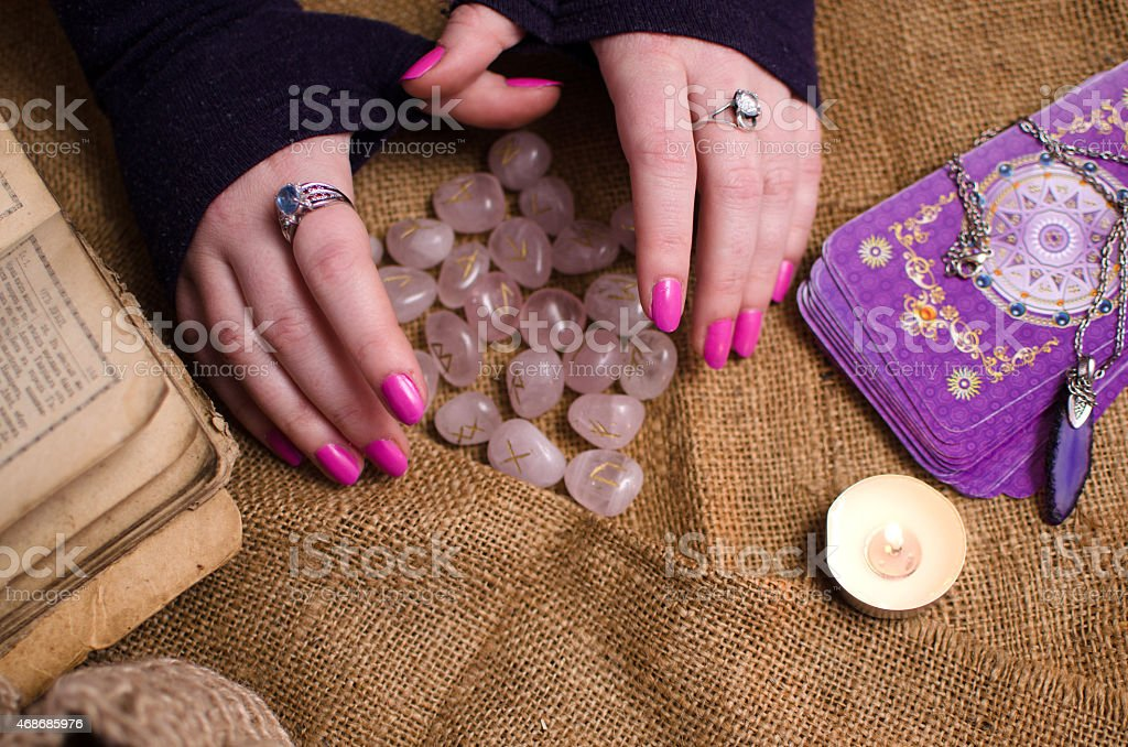 female hand holding a magic rune stone stock photo
