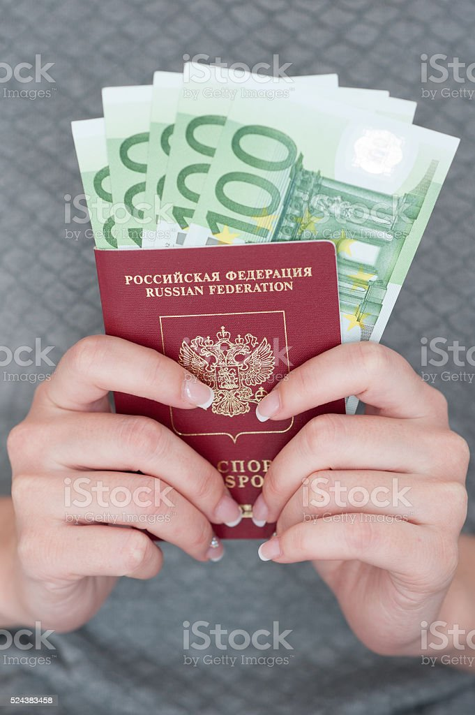 female hand holding a passport with Euro banknotes. stock photo