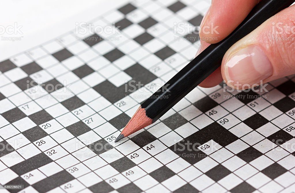 female hand holding a pencil and solves crossword puzzle stock photo
