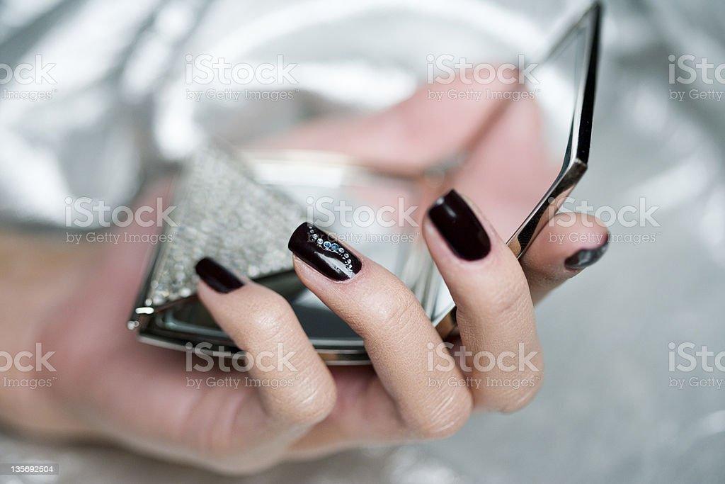 female hand holding a pocket mirror royalty-free stock photo