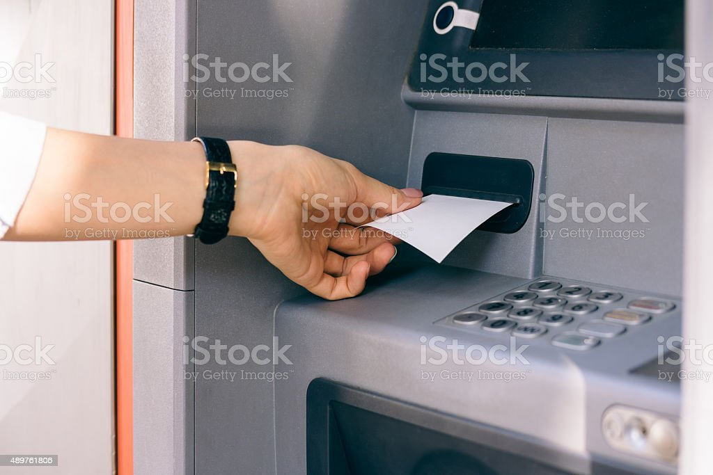 Female hand holding a receipt obtained from the ATM stock photo