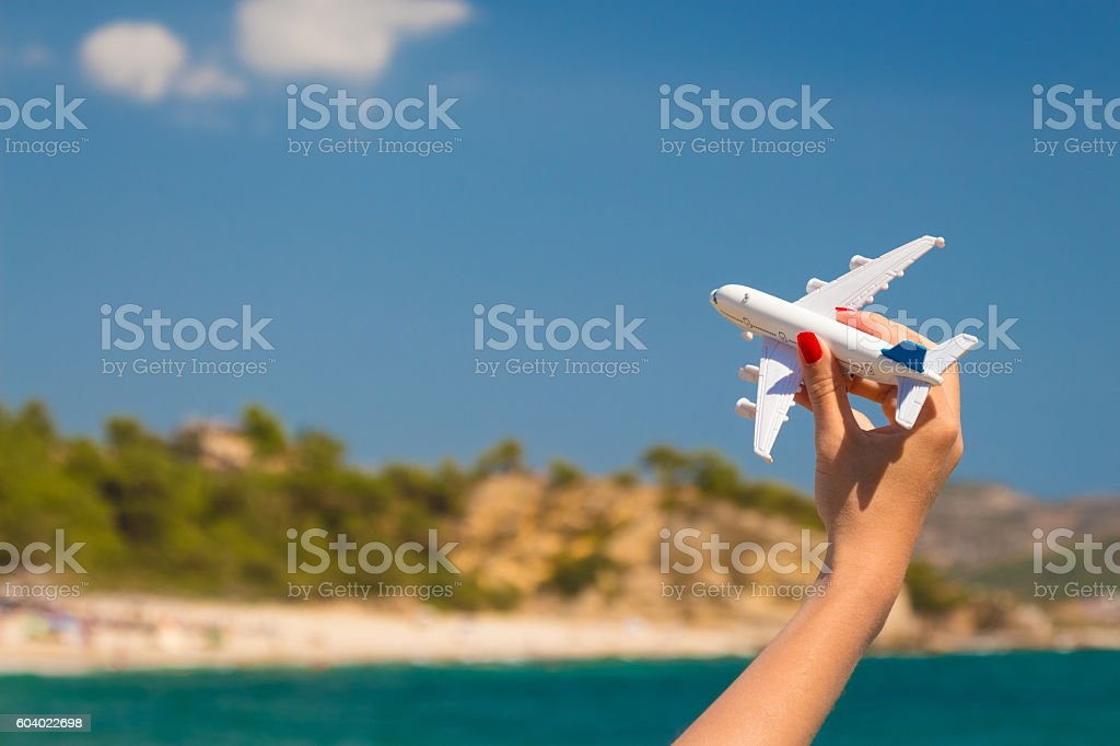 Female hand holding airplane toy at the beach stock photo