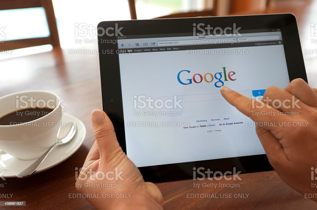 Female hand holding an ipad showing Google. stock photo