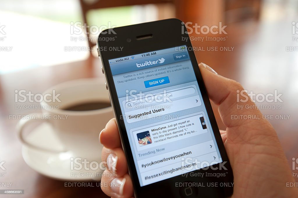 Female hand holding an iphone showing Twitter stock photo