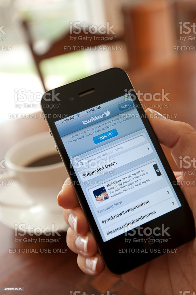 Female hand holding an iphone showing Twitter royalty-free stock photo