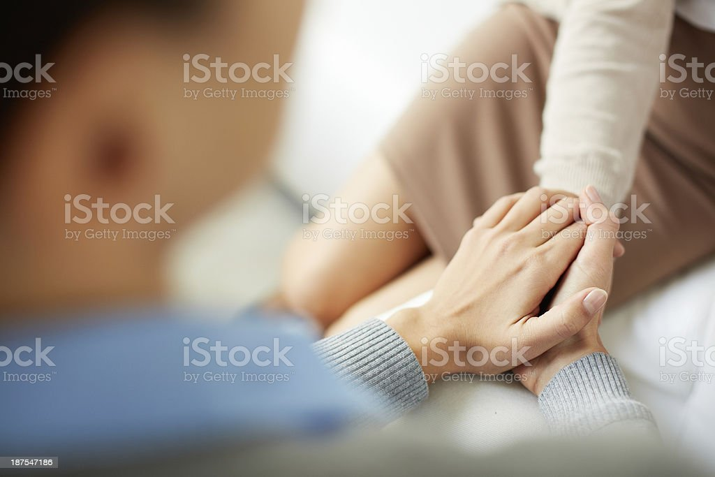 Female hand holding another female's hand stock photo