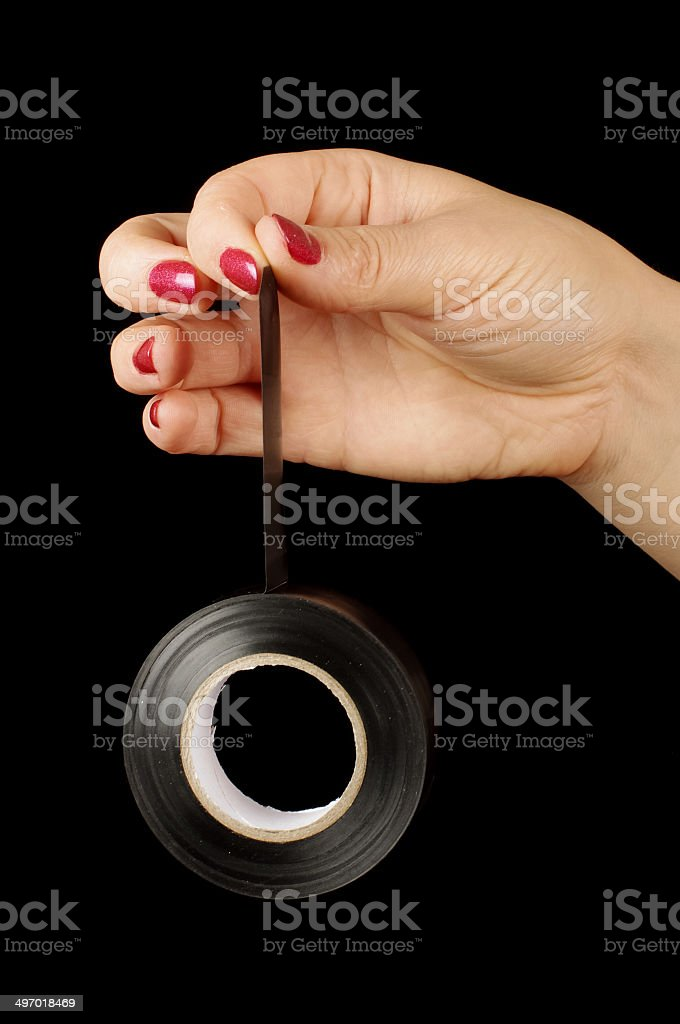 Female hand holding black gaffer tape roll stock photo