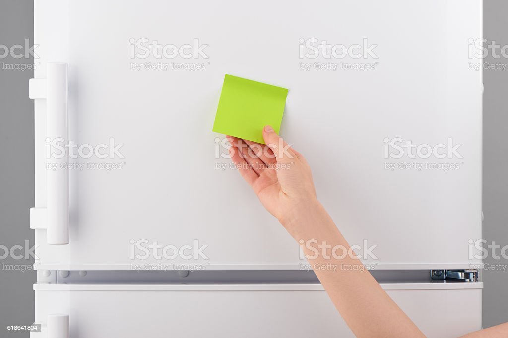 Female hand holding blank green paper note on white refrigerator stock photo