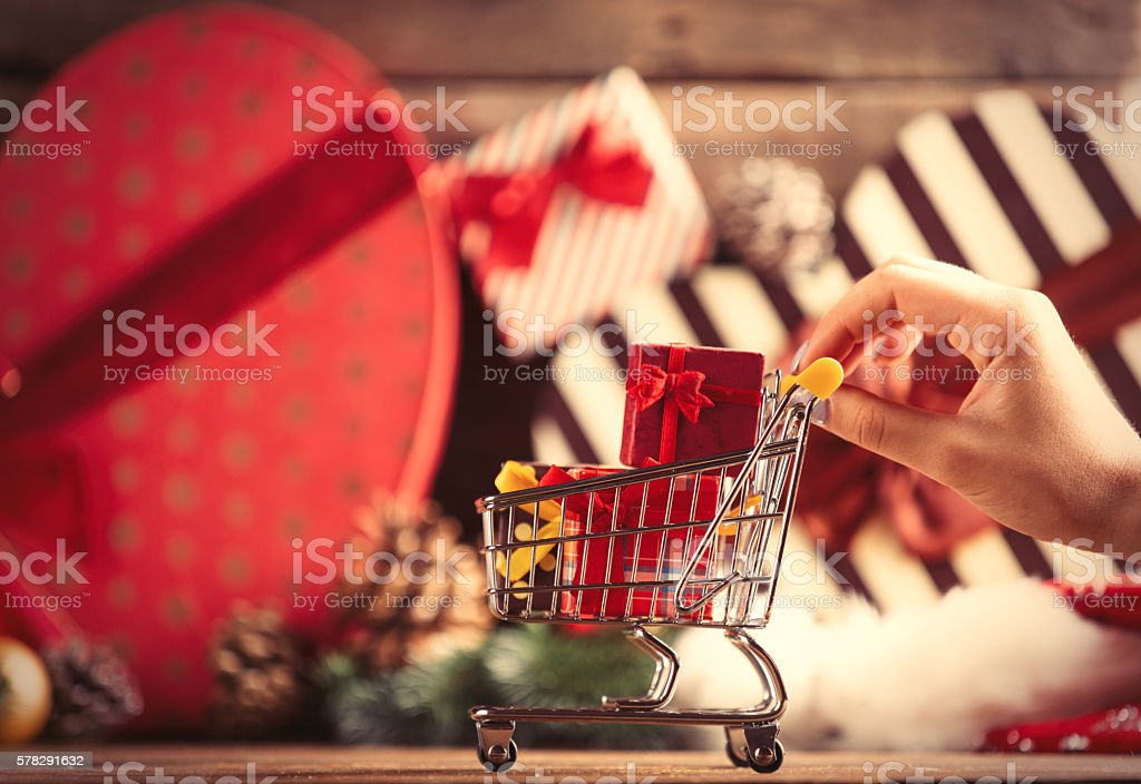 female hand holding cart with gifts stock photo