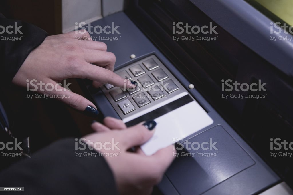 Female hand holding credit card next to the ATM stock photo