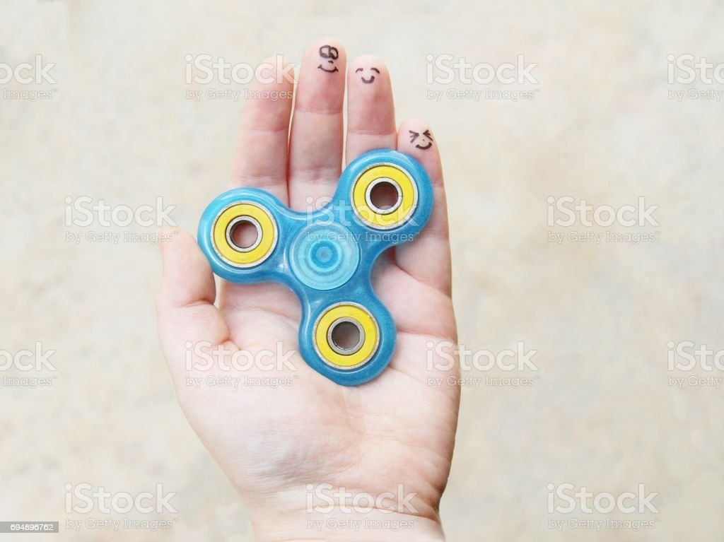 Female hand holding fidget spinner toy with faces drawn on fingers stock photo