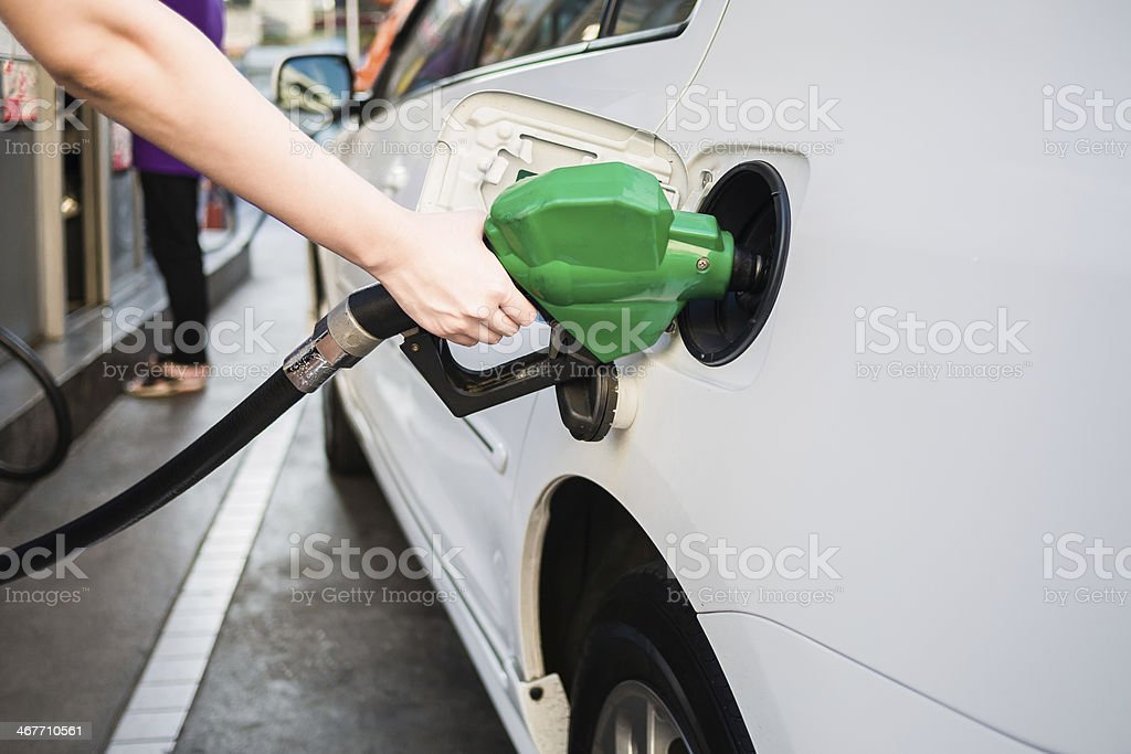 Female hand holding green pump filling gasoline stock photo