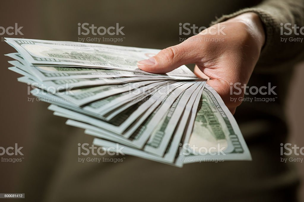 Female hand holding many dollar's banknotes stock photo