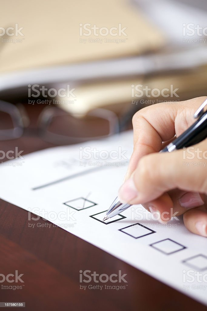 Female hand holding pen about to make a check mark on paper stock photo