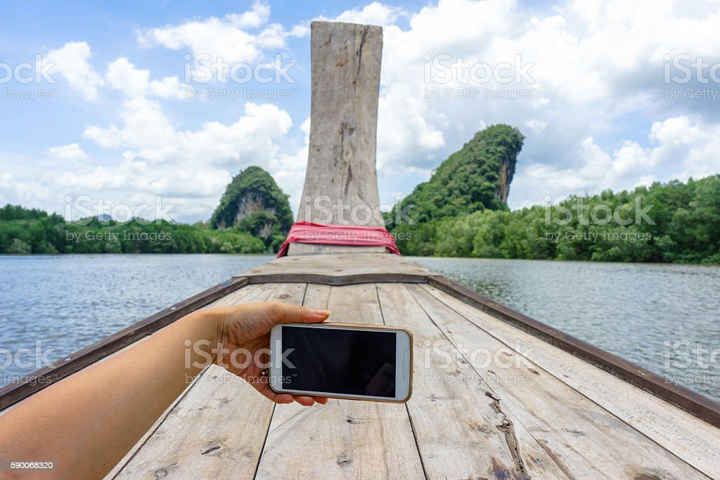 Female hand holding phone in boat photo libre de droits