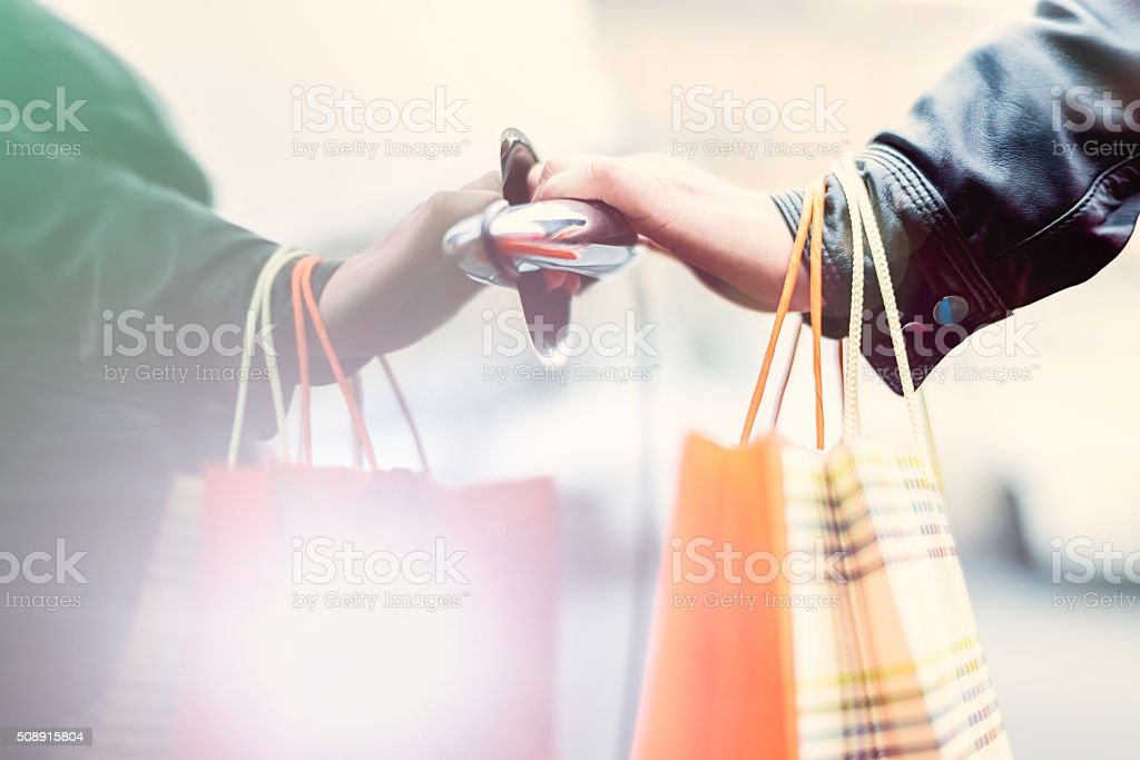 Female hand holding shopping bags and opening car's door stock photo