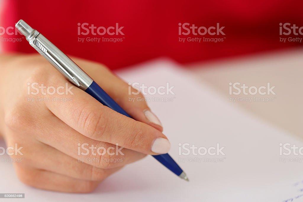 Female hand holding silver pen closeup stock photo
