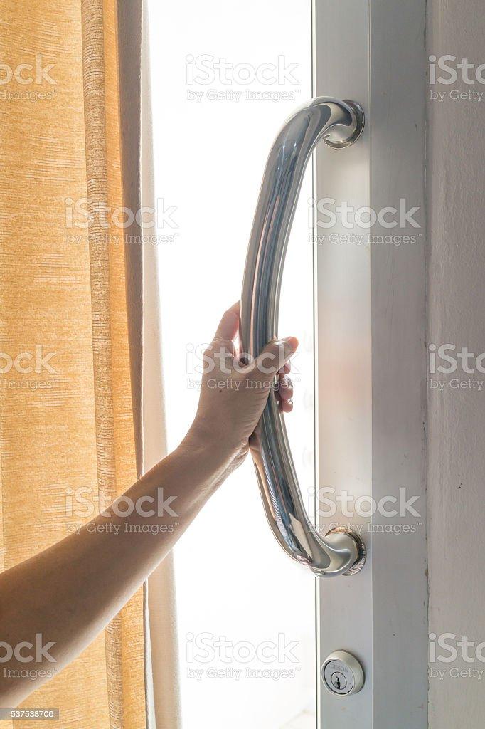 Main d'une femme tenant en acier Cale-porte photo libre de droits