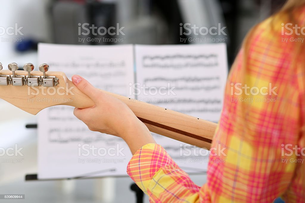Female hand holding wooden neck of electric guitar stock photo