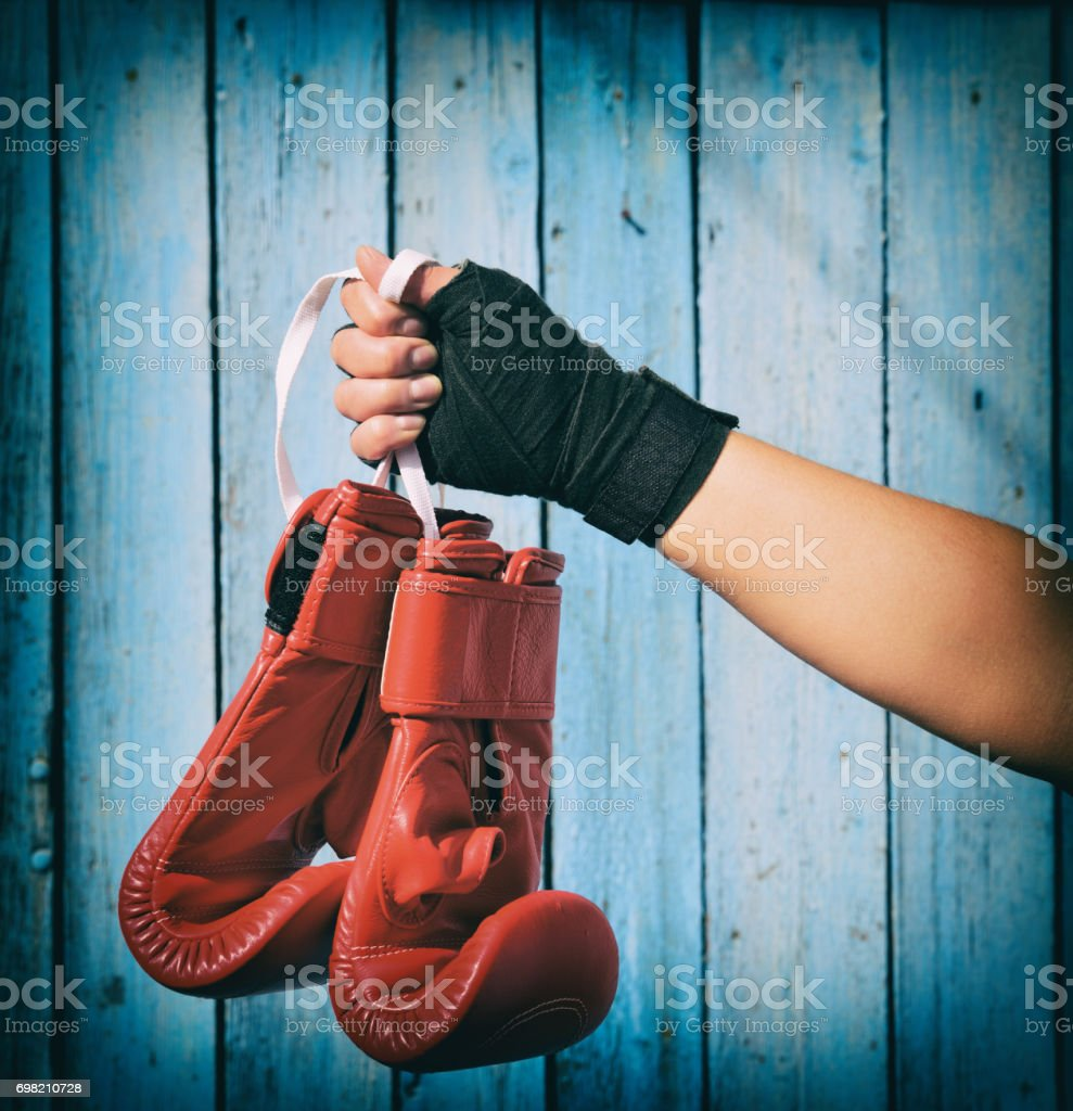 Female hand holds a pair of red kickboxing gloves stock photo
