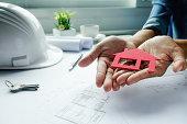 Female hand holds house model