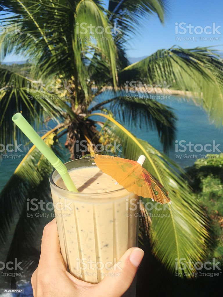 Female hand holds tropical fruit smoothie stock photo