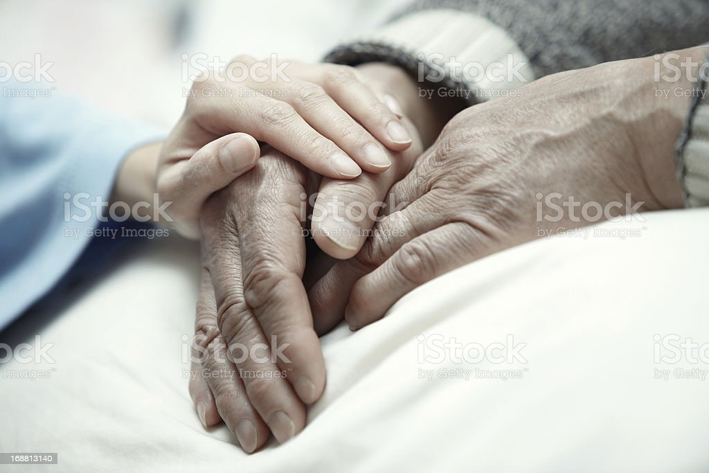 A female hand in clinic  touches elderly hands stock photo